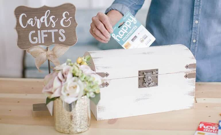 Putting a gift card into the wedding gift card box
