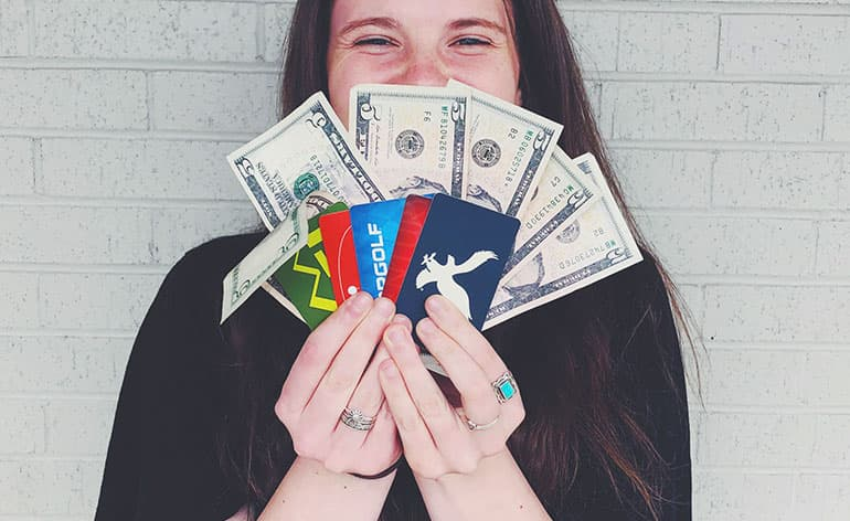 girl holding gift cards and cash
