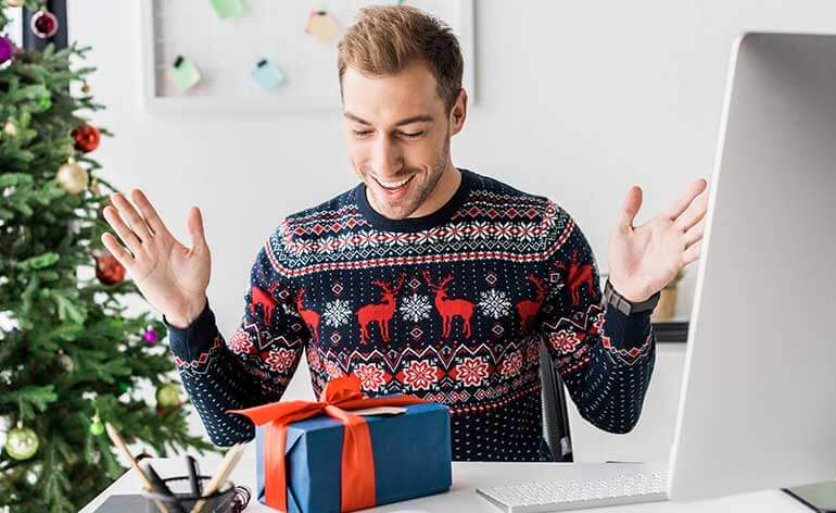 man opening a holiday gift at office