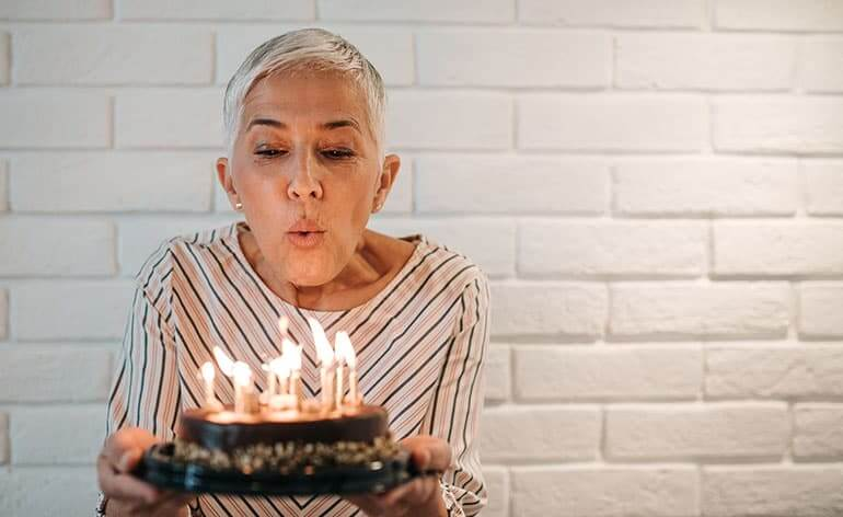 senior woman blowing out candles