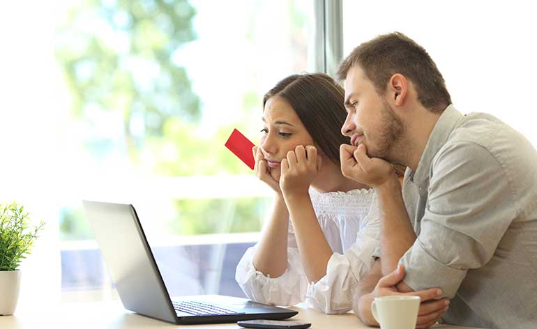 couple waiting for card to work on computer